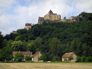 Castelnaud castle - Medieval fortress dominating trees and houses, clouds in the sky, in the Dordogne valley, in Périgord