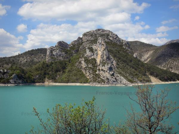 Castillon lake - Emerald-coloured lake (water reservoir), trees, shore and mountains; clouds in the blue sky; in the Verdon Regional Nature Park