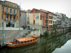 Castres - The River Agout with a wooden boat moored to the quay and houses reflected in water