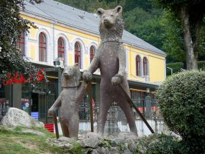 Cauterets - Spa town and health resort : statue des Ours au ski (sculpture) on the Esplanade des Oeufs square, facade of the Casino in the background