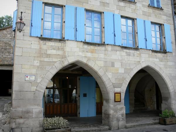 Caylus - Arcaded stone house with blue shutters of the Place de la Mairie square