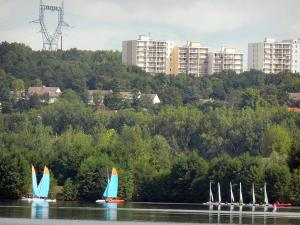 Cergy-Pontoise sports and recreation park - Water sports on one of the lake of the domaine, trees along the water, houses and buildings in background