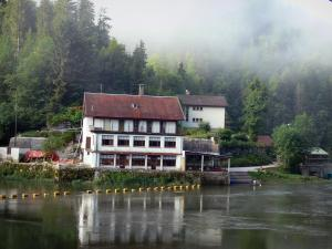 Chaillexon lake - Lake, shore, houses and trees of the forest in the mist