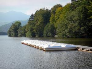 Chambon lake - Lake, pedal boats, trees along the water and hills in the background; in the Auvergne Volcanic Regional Nature Park, in the Monts Dore mountain area