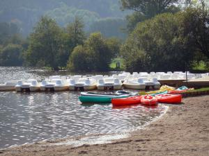 Chambon lake - Beach, canoes, pedal boats and trees lining the water; in the Auvergne Volcanic Regional Nature Park in the Monts Dore mountain area