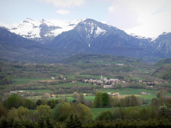 Champsaur valley - Church and houses of the village of Saint-Julien-en-Champsaur, prairies, trees and mountains with snowy tops (snow)