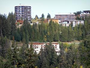 Chamrousse - Recoin (Chamrousse 1650): buildings and trees of the ski resort in autumn