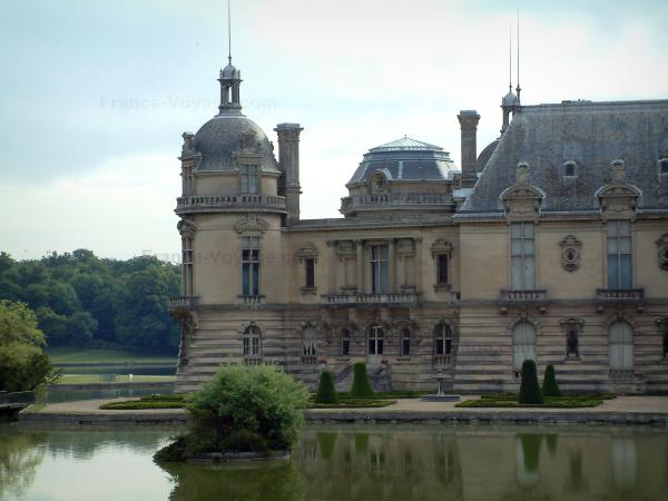 Chantilly - Pond, Château de Chantilly, flowerbeds and trees of the forest in background