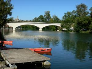 Charente valley - Bridge spanning the Charente river, trees along the water, pontoon, canoes, Saint-Simeux church overhanging the set