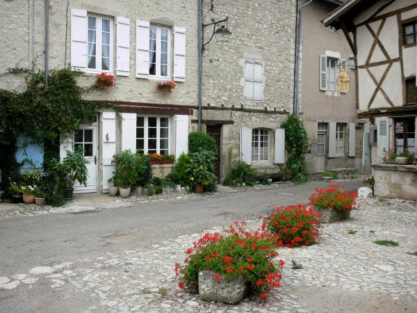 Charroux - Facades of houses and floral decorations (flowers) of the Rue de l'Horloge street; in Bourbonnais