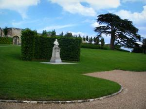 Château d'Amboise - Bust of Leonardo da Vinci, trees and lawn of the park, clouds in the blue sky