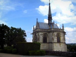 Château d'Amboise - Saint-Hubert chapel of Flamboyant Gothic style, trees and hedges, clouds in the sky