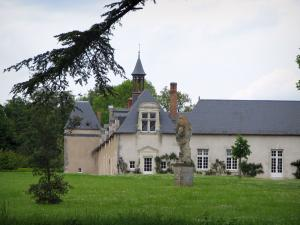 Château de Beauregard - Branches of a tree in foreground, prairie, statue and outbuildings of the Château