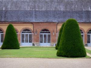 Château de Bouges - Facade of the Orangery and clipped shrubs; in the town of Bouges-le-Château