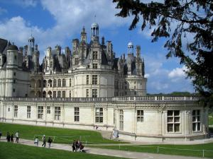 Château de Chambord - Branches of a tree in foreground, Renaissance Château, alley lined with lawns, and clouds in the blue sky