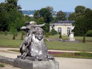 Château de Champs-sur-Marne - Park of the château: Sphinx statue in the foreground, flowerbeds, lawns, shrubs, trees and orangery