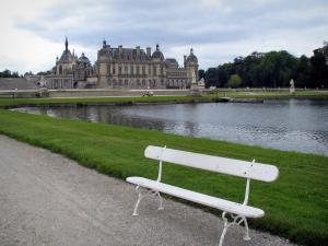 Château de Chantilly - Park: French-style formal garden of Le Nôtre: bench in foreground, La Manche, lawns and château