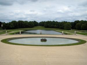 Château de Chantilly - Park: French-style formal garden of Le Nôtre: Gerbe ornamental lake, La Manche, statues, flowerbeds, and trees of the park in background