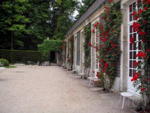 Château de Chantilly - Park: facade of Sylvie's house decorated with red roses (climbing roses)