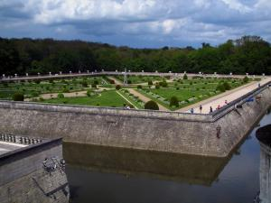 Château de Chenonceau - Diane de Poitiers garden with its fountain, its shrubs and its formal flowerbeds, moats, trees and clouds in the sky