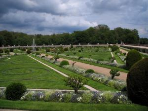 Château de Chenonceau - Diane de Poitiers garden with its fountain, its shrubs and its formal flowerbeds, trees and clouds in the sky