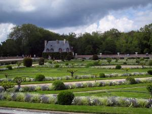 Château de Chenonceau - Formal flowerbeds and shrubs of the Diane de Poitiers garden, Chancellery, trees and clouds in the sky