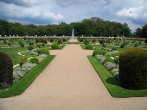 Château de Chenonceau - Diane de Poitiers garden with its paths, its fountain, its formal flowerbeds and its shrubs, trees and clouds in the sky
