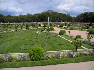 Château de Chenonceau - Diane de Poitiers garden with its formal flowerbeds, its fountain and its shrubs, trees and clouds in the sky