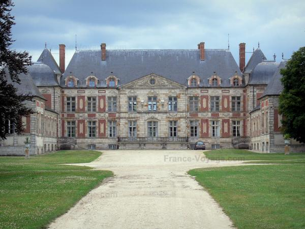 Château de Courson - Facade of the château and alley lined by lawns; in the town of Courson-Monteloup