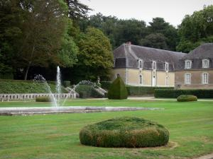 Château de la Lorie - Garden featuring a fountain and water jets, outbuildings and wing of the Château, trees, in Chapelle-sur-Oudon
