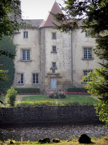 Château des Martinanches - Stair tower and facade of the castle, flower garden, moats and trees; in Saint-Dier-d'Auvergne, in the Livradois-Forez Regional Nature Park