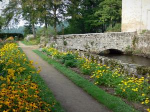 Château des Martinanches - Alley lined with flowers and small bridge spanning the moat; in Saint-Dier-d'Auvergne, in the Livradois-Forez Regional Nature Park