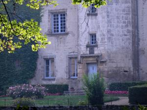 Château des Martinanches - Stair tower and facade of the castle, garden flowers and branches of a tree; in Saint-Dier-d'Auvergne