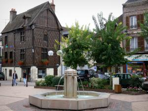 Château-Renard - République square featuring a fountain, Joan of Arc's house (old half-timbered house), trees, flowers and houses of the city