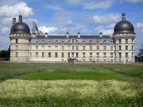Château de Valençay - Facade of Classical style, corner towers of the château, and patchwork of meadow flowers of the park; clouds in the blue sky
