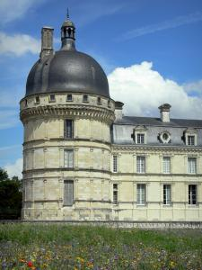 Château de Valençay - Corner tower and facade of the Classical-style château, patchwork of meadow flowers of the park; clouds in the blue sky