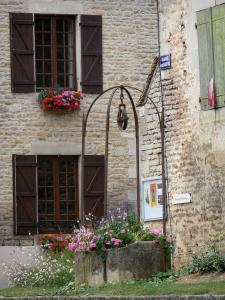 Châteauvillain - Flower-bedecked well and facades of the small medieval town