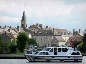 Châtillon-en-Bazois - Leisure boat sailing on the Nivernais canal, bell tower of the Saint-Jean-Baptiste church and houses of the village