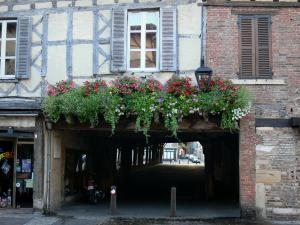 Châtillon-sur-Chalaronne - Facade of a timber-framed house, and flower-bedecked entrance of the covered market hall