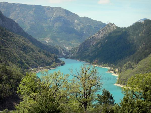 Chaudanne lake - Trees in foreground with view of the emerald-coloured lake (water reservoir) surrounded by mountains; in the Verdon Regional Nature Park