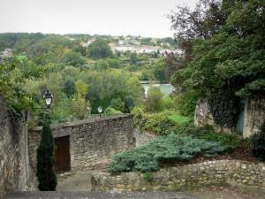 Chauvigny - Stone walls and trees with view of the expanse of water of the public garden