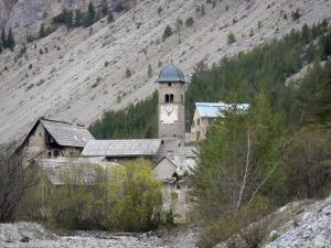 Clarée valley - Village of Plampinet: bell tower of the Saint-Sébastien church, houses, trees and hillside