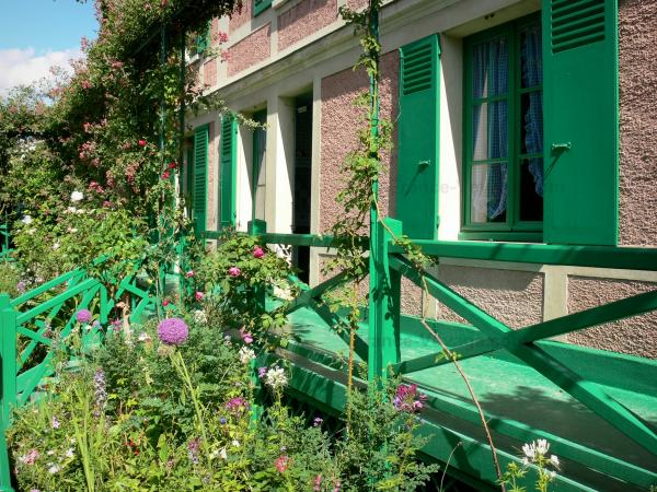 Claude Monet's house and gardens - Monet's pink house with green shutters and its surroundings with flowers; in Giverny