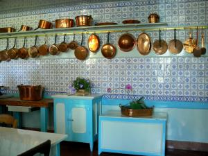 Claude Monet's house and gardens - Inside Monet's house, in Giverny: kitchen with blue tiles and copper utensils