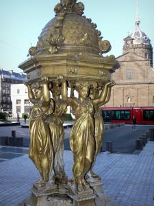 Clermont-Ferrand - Caryatids of the Wallace fountain, Jaude square, dome of the Saint-Pierre-les-Minimes church and tram in the background