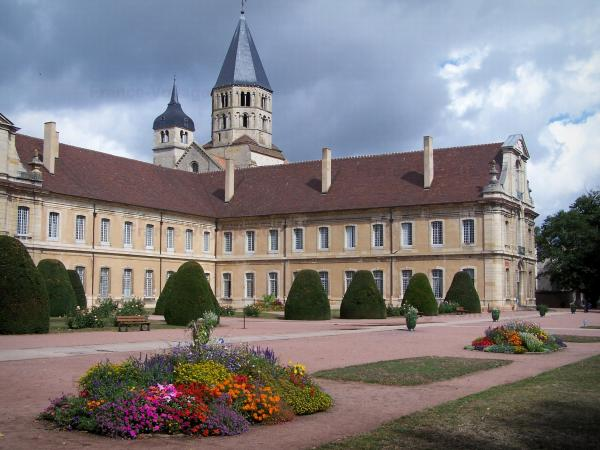 Cluny abbey - Benedictine abbey: the Eau Bénite bell tower and the Clock tower (remains of the Saint-Pierre-et-Saint-Paul abbey church), convent buildings, garden featuring flowerbeds and cut shrubs; heavy sky