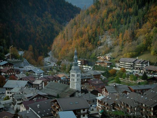 La Clusaz - View of the church and houses (chalets) of the village (winter and summer sports resort), mountains covered with trees in autumn