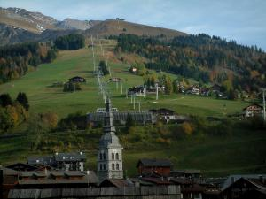 La Clusaz - Church bell tower and chalets of the winter and summer sports resort, alpine pastures (high meadows), ski area with ski lifts and trees in autumn