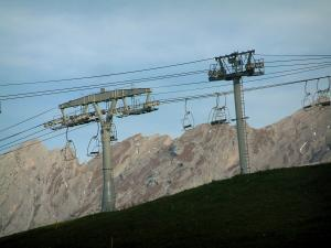 La Clusaz - Alpine pasture (high meadow), ski lift (chairlift) of the resort and the Aravis massif