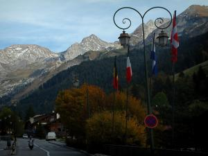 La Clusaz - Avenue of the resort (village) with its lampposts and its flags, trees in autumn, forest and the Aravis massif